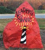 "Red rock with words ""Leaders Shine"" and lighthouse"
