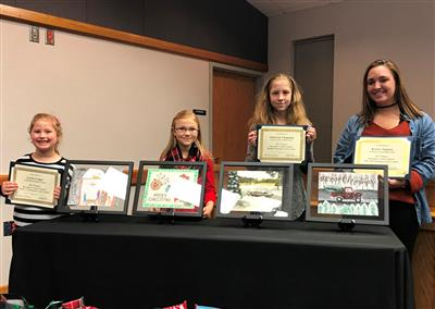 Photo of the 2017 Christmas Card Contest Winners with their artwork.