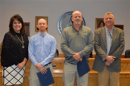 Photo of Tyler Mitchell and JD Sink with Superintendent Dr. Jennifer Hefner and School Board Member