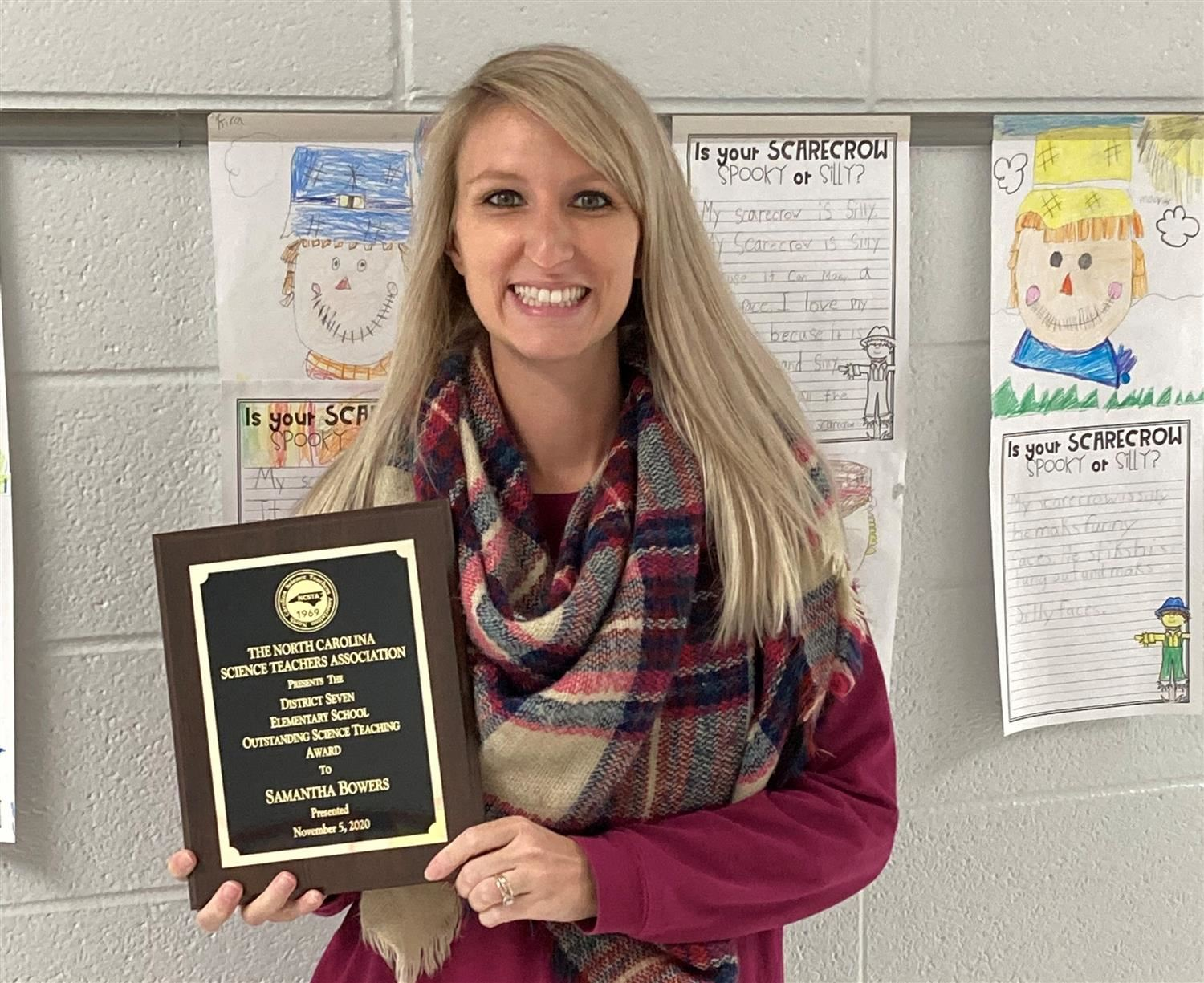 Photo of Samantha Bowers with plaque for Outstanding Science Teacher of the Year
