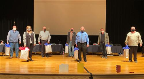 School board members on stage with gifts
